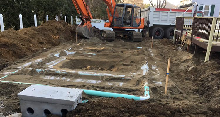 Distribution box and pipes are visible before Grenco Septic Systems and Excavation covers them with dirt in a back yard in Rhode Island.