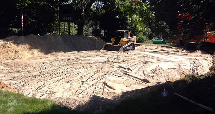 Grenco uses a small front loader to smooth out dirt for an are where a septic system was installed and the area was excavated.