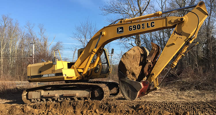Grenco Septic Systems and Excavation has this massive John Deere backhoe ready to work on the job site to remove large boulders and stones.
