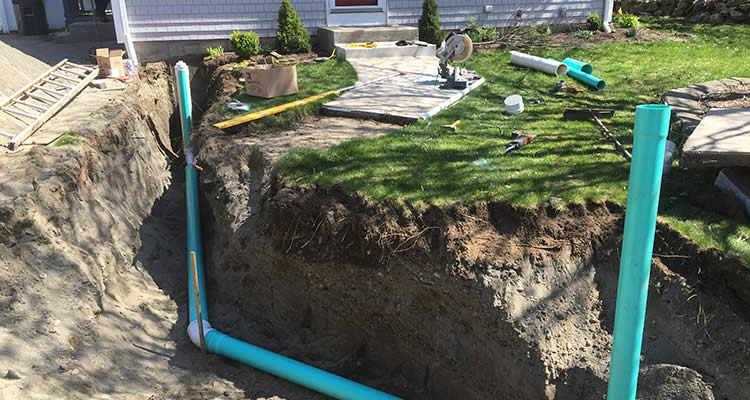 The excavated section in front of a Rhode Island home that shows septic system pipe and the area excavagted by Grenco Septic Systems and Excavation