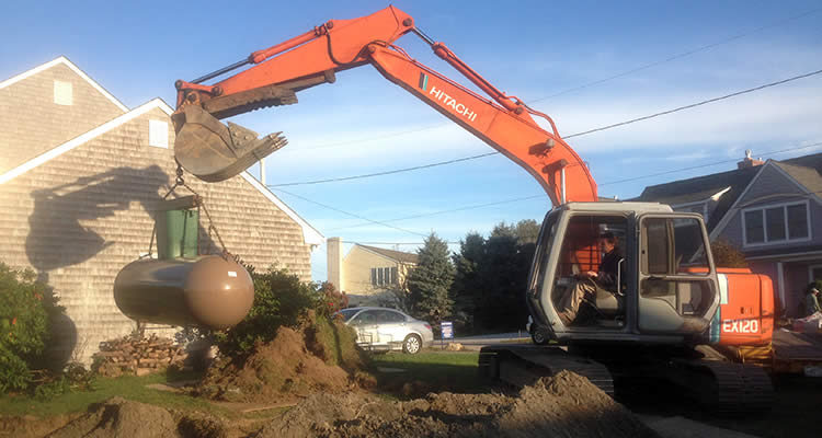 Grenco Septic Systems and Excavation uses the Hitachi to lower a tank into an excavated area.