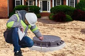 Man kneeling down and inspecting a septic system.